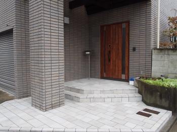 色合いがシックな床タイルと防犯、断熱性能が高い木目調の玄関ドア。格調高い玄関ポーチが完成しました。